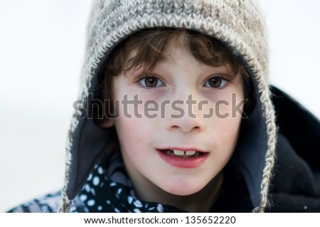 close up of an eight year old boy wearing a woolly winter hat outdoors in the snow - stock photo
