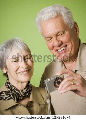 Close-up of an elderly couple looking at a digital camera