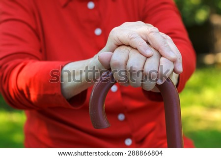 Close up of an elderly hand holding a cane - stock photo
