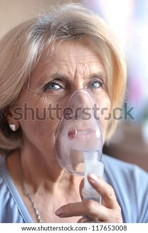 close-up of an elderly woman doing inhalation - stock photo