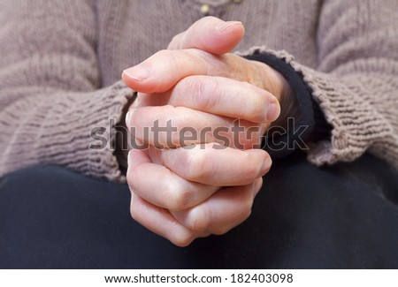 Close up of an elderly woman holding her hands - stock photo