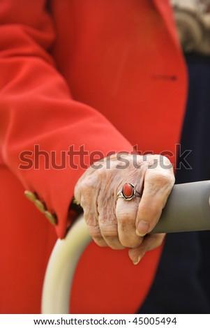 Close-up of an elderly woman's hand on her walker.  Vertical shot. - stock photo