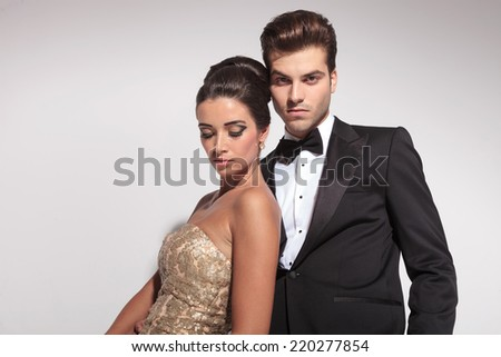 Close up of an elegant couple posing on grey studio background, the woman is leaning on her lover looking down, while he is looking at the camera. - stock photo