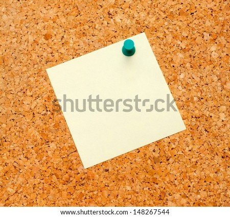 Close up of an empty yellow notice label on cork-board