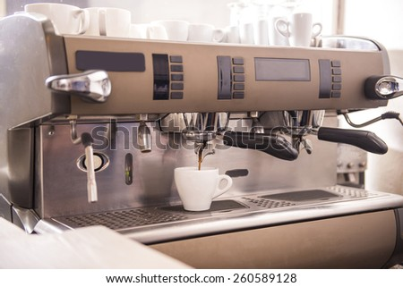 Close-up of an espresso machine making a cup of coffee. - stock photo