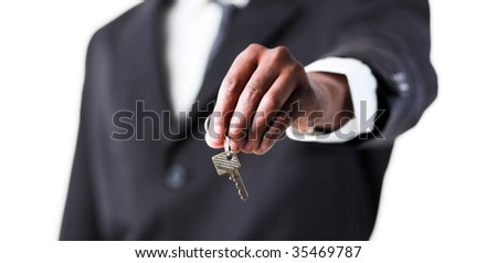 Close-up of an ethnic businessman holding a key - stock photo