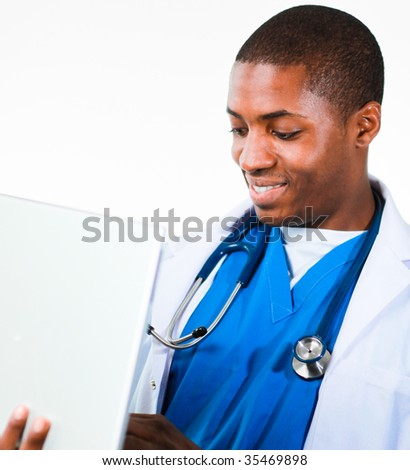 Close-up of an friendly Afro-American doctor working on a laptop wearing scrubs and coat isolated against white - stock photo