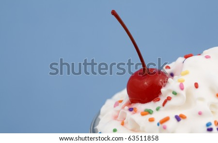 Close-up of an Ice Cream Sundae with rainbow sprinkles, and a cherry on top! - stock photo