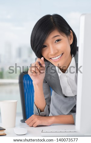 Close-up of an office assistant smiling and looking at camera