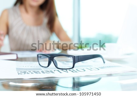 Close-up of an office workplace, business lady can be seen in the background - stock photo