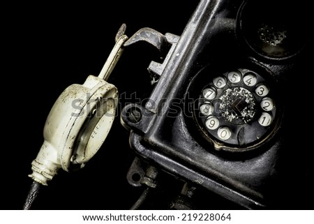 Close-up of an old black telephone isolated on a black background