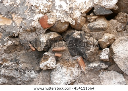 Close up of an old broken cement wall with colored stones and holes.