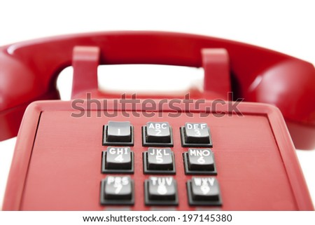 Close-up of an old-fashioned, red, push-button plastic telephone. - stock photo