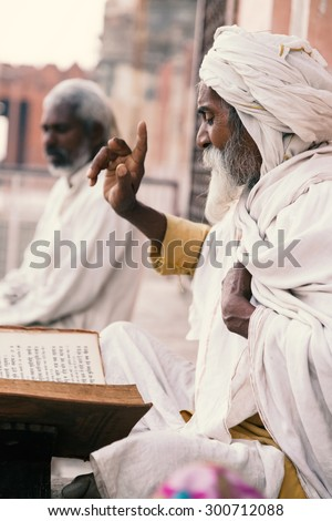 Close up of an old indian sadhu (saints) sitting and reading sacred texts near the temple. Varanasi (India) on 23 Nov 2014.