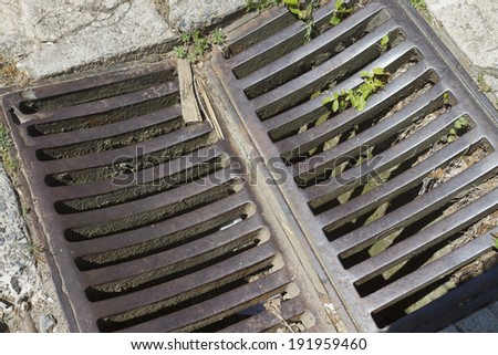 Close up of an old, metal street storm drain grate - stock photo