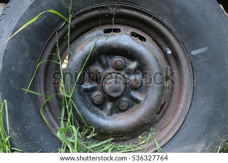 close up of an old wheel with a rusted hub cap and grass growing around it
