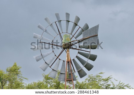 Close up of an old wind water pump against a dark stormy sky - stock photo