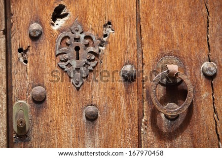 Close up of an old wooden door with an old filigree metal lock, studs and an iron ring handle alongside a small modern cylinder lock - stock photo