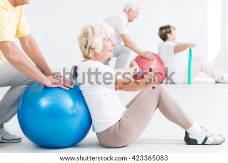 Close-up of an optimistic elderly lady exercising using resistance band, assisted by her partner