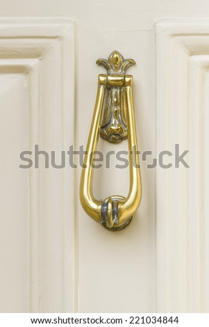 Close up of an polished elegant brass door knocker on a white painted wooden door - stock photo