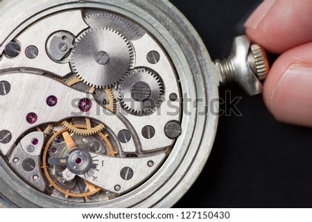 Close up of analog clock mechanics with finger winding it up - stock photo