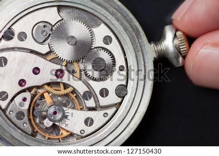 Close up of analog clock mechanics with finger winding it up - stock photo
