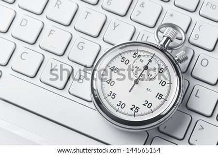 Close up of analog stopwatch on a laptop keyboard with copy space - stock photo