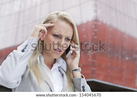 Close-up of angry businesswoman conversing on cell phone against office building - stock photo
