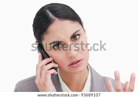 Close up of angry businesswoman on her cellphone against a white background - stock photo