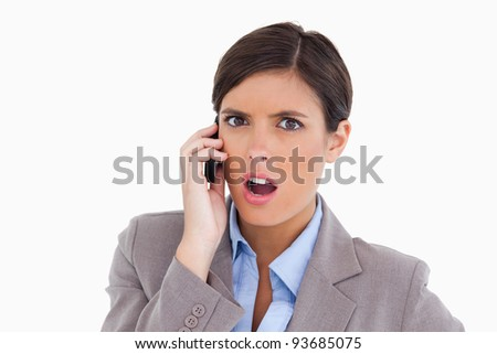 Close up of angry female entrepreneur on her cellphone against a white background - stock photo