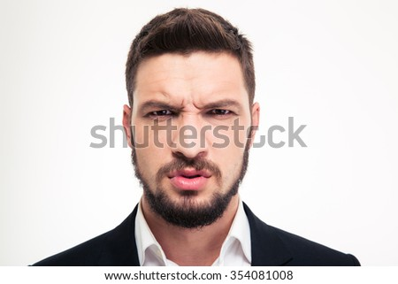 Close up of angry irritated bearded young business man in black suit and white shirt looking camera over white background - stock photo