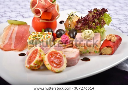 Close up of antipasto and catering platter with different appetizers(fruits, vegetables, meats, cheeses)on white and purple background - stock photo
