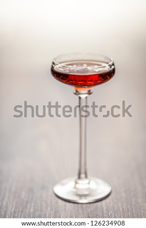 Close-up of antique glass with liqueur on wooden table. - stock photo