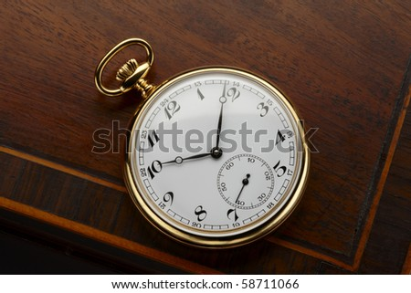 close up of antique pocket watch shot on antique wooden surface, space for copy