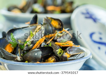 Close Up of Appetizing Fresh Mussels in Small Single Serving Bowl Positioned in front of Ceramic Serving Bowl and Served on Blue Table with Placemat