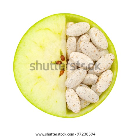 Close up of apple and pills isolated - vitamin concept