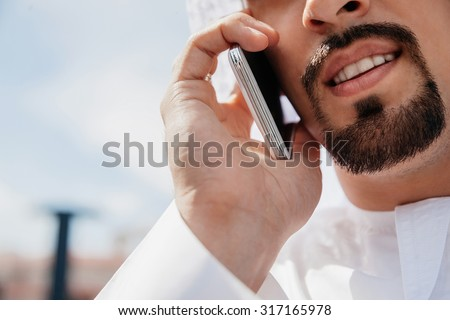 Close Up Of Arabian Male Using Smart Phone Outdoors. Focus Is On Smart Phone - stock photo