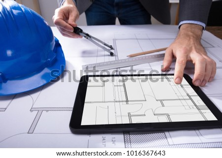 Architects scale stock images royalty free images vectors close up of architects hand using digital tablet with blueprint on desk malvernweather Gallery