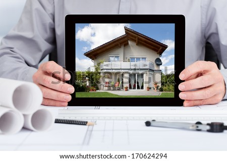 Close-up Of Architect Showing Picture Of House On Digital Tablet - stock photo