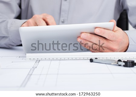 Close-up Of Architect Using Digital Tablet  Over Blueprint - stock photo