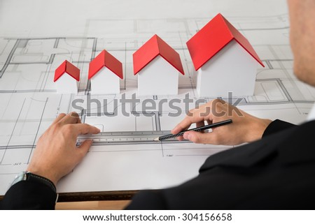 Close-up Of Architect With Different Size House Models On Blueprint In Office - stock photo