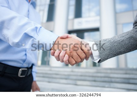 Close up of arms of colleagues shaking hands. The man and woman are standing near building outside - stock photo