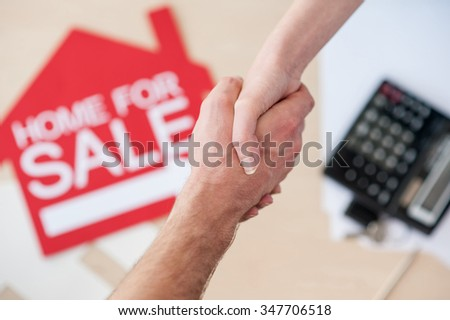 Close up of arms of estate agent and client shaking hands under the table - stock photo