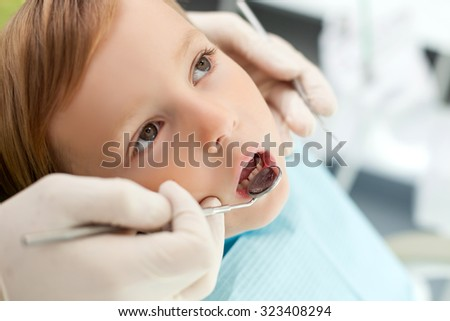 Close up of arms of male dental doctor. The man is holding tools and examining teeth of child. The boy is sitting in chair and opening his mouth. He is looking up seriously - stock photo