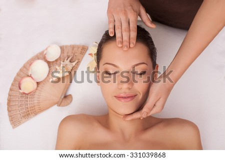 Close up of arms of masseuse massaging female forehead and chin. The young beautiful woman is getting head massage with pleasure. She is lying and smiling - stock photo