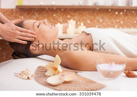 Close up of arms of masseuse massaging female head at spa. She is standing and touching hair of client. The beautiful young woman is lying and smiling - stock photo