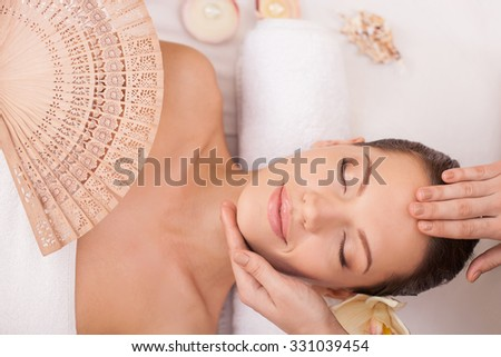 Close up of arms of masseuse massaging head of woman. She is standing and touching female forehead and chin. The young girl is lying and smiling. Her eyes are closed with pleasure - stock photo