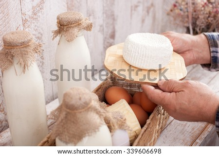 Close up of arms of old man carrying the healthy cheese. There are a basket with bottle of milk and eggs on the table - stock photo