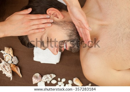 Close up of arms of professional masseuse massaging male head. The man is lying and smiling at spa - stock photo