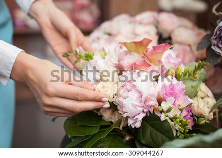 Close up of arms of skilled saleswoman making beautiful bouquet in workshop